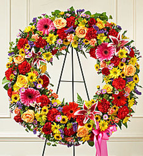 """•Standing wreath of fresh, bright red and peach roses arranged with lilies, Gerbera daisies, carnations, poms, hypericum and more •Appropriate for family, friends and business associates to send directly to the funeral home •Our florists use only the freshest flowers available, so colors and assortment may vary •Large arrangement measures approximately 34""""H x 34""""W without easel •Small arrangement measures approximately 32""""H x 32""""W without easel"""