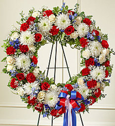 •Standing wreath arrangement of fresh red and white roses and carnations, blue delphinium and more •Accented by vibrant greenery •Appropriate for family, friends and business associates to send directly to the funeral home •Our florists use only the freshest flowers available, so colors and assortment may vary