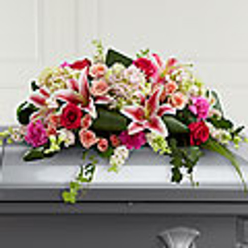 includes larkspur, roses, carnations, hydrangeas and Stargazer lilies complemented with lush greens including aspidistra, salal and ivy vines. It is made to fit over the closed portion of a casket cover during visitation at a funeral home, at a funeral service and at a graveside ceremony at the cemetery.
