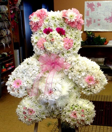 This custom one of a kind Teddy Bears is created with a variety of white Fuji mums, white carnations, white poms, lavender buttons, and pink daisies.  (LOCAL DELIVERY ONLY)