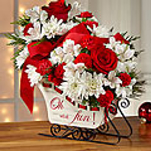"A modern, fresh take on the traditional sleigh arrangement, we bring together red roses, red carnations, and red mini carnations, offset by snowy white Peruvian lilies and chrysanthemums, accented with an assortment of Christmas greens. Presented in a white holiday sleigh, that reads, ""Oh, what fun!"" on the side in a scrolling red font"