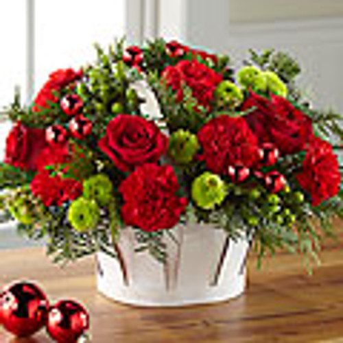 Rich red roses, red mini carnations, white chrysanthemums, green button poms, variegated holly, and an assortment of holiday greens are artistically arranged to blossom from a stylish red rectangular ceramic vase tied with a festive Santa ribbon to give it the look of a holiday present.