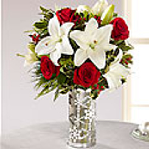 White Asiatic lilies stretch their star-shaped petals across the length of this flower arrangement surrounded by rich red roses, variegated holly, and an assortment of Christmas greens, perfectly matched with an enchanting snowflake inspired glass vase with shimmering silver accents