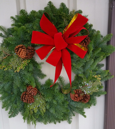 "24"" mixed noble pine wreath with a bow and pine cones."