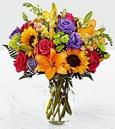 This gorgeous fresh flower arrangement brings together sunflowers, hot pink roses, purple double lisianthus, orange LA Hybrid Lilies, yellow snapdragons, green button poms, and lush greens