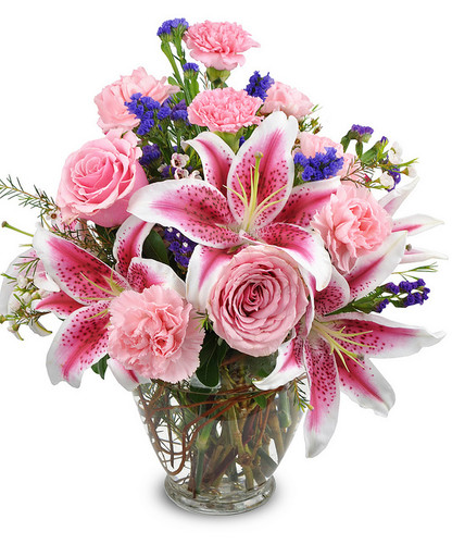 Filled with blushing light pink roses, carnations and stargazer lilies with accents of purple filler all clustered together in a clear glass vase. This soft and sweet design is a perfect way to convey your message.