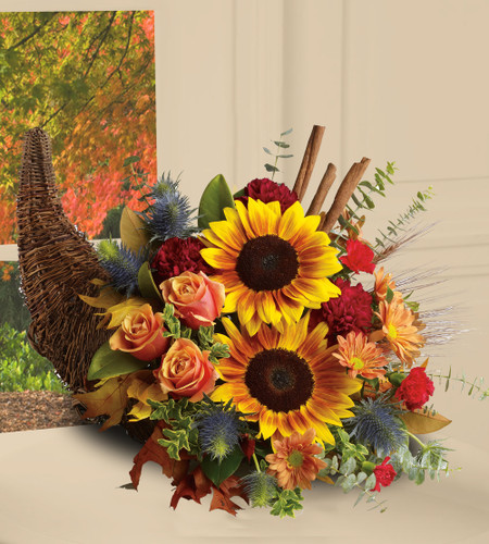 The Flowerloft's Classic Cornucopia features dazzling sunflowers, light orange roses and spray roses, red daisy spray chrysanthemums, yellow cushion spray chrysanthemums, eucalyptus, magnolia leaves, cinnamon sticks and wheat are perfectly arranged in a wicker cornucopia.