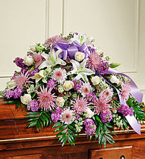 "•Half casket cover arrangement of fresh long stem white roses and oriental lilies, lavender cremones, stock and more. •Traditionally sent by the immediate family to the funeral home •Our florists use only the freshest flowers available, so colors and varieties may vary •Arrangement measures approximately 16""H x 26""D x 38""L"