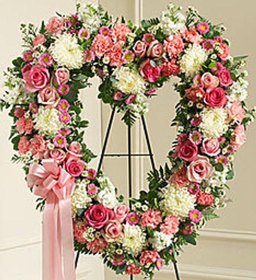 """•Floral heart arrangement of fresh pink and white flowers, including roses, stock, carnations and more •Comes on a wire easel with accents and satin ribbon •Appropriate for family and friends to send directly to the funeral home •Our florists use only the freshest flowers available, so colors and varieties may vary •Measures approximately 34""""H x 32""""L without easel"""