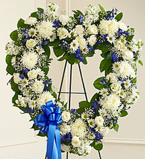 """•Heart-shaped arrangement of fresh blue and white flowers such as roses, delphinium, carnations and more •Comes on a wire easel with accents and satin ribbon •Appropriate for family or friends to send directly to the funeral home •Our florists use only the freshest flowers available, so colors and varieties may vary •Measures approximately 28""""H x 28""""L without easel"""