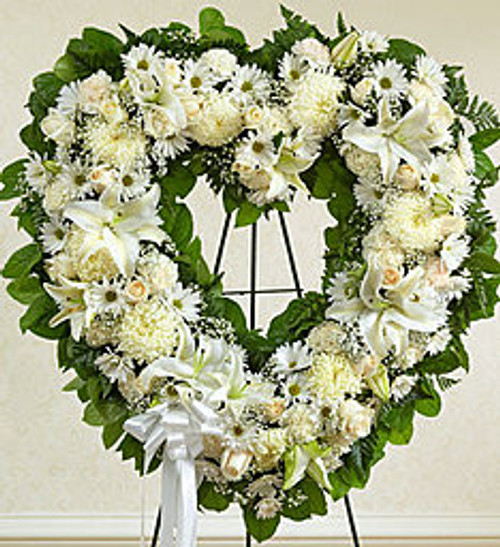 """•Heart-shaped arrangement of fresh white roses, lilies, carnations and more •Accented by baby's breath, salal and leather leaf and finished off with a satin ribbon •Comes on a wire easel with accents and satin ribbon •Appropriate for family and friends to send directly to the funeral home •Our florists use only the freshest flowers available, so colors and assortment may vary •Measures approximately 34""""H x 32""""W without easel"""