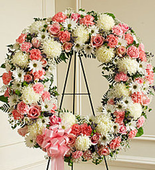 This standing wreath, crafted from exquisite pink and white roses, carnations and more, beautifully reflects all the love and sympathy that is in your heart.