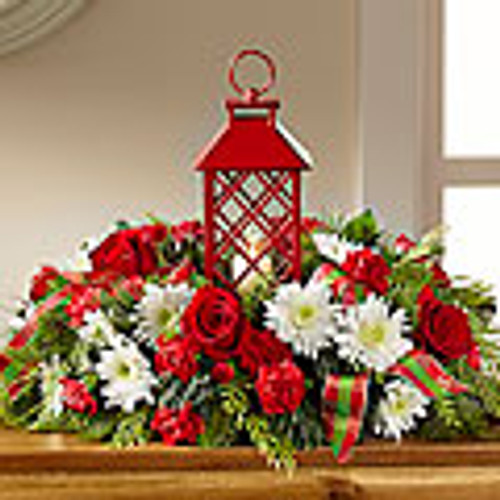 Red roses, carnations, and mini carnations are beautifully arranged amongst white chrysanthemums, and an assortment of holiday greens all surrounding an attractive red lantern with a lattice pattern housing a single white votive candle.