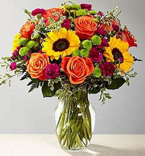 Our floral professionals weave together a blend of orange roses, sunflowers, violet mini carnations, green button poms, and lush greens to create an incredible gift. Presented in a clear glass vase.