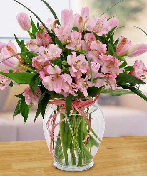 We have combined the pink petals of tulips and Alstroemeria lilies and a pink bow for a soft, fresh look.