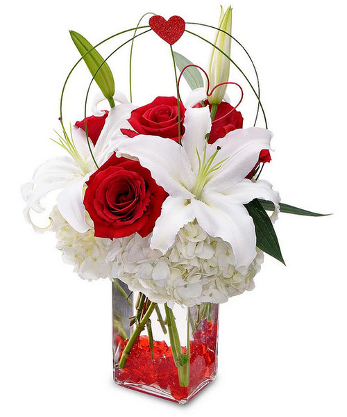 """Vivid red roses, vibrant large white lilies, and fluffy white hydrangeas highlight this red-hot design. Perfect for your anniversary, or simply to say, """"I love you,"""" this special design will warm the heart and brighten anyone's day with its clear rectangular vase, bright red rocks and heart-shaped decorations."""