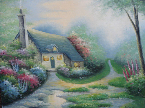 Beautiful medium sized painting on canvas, stretched but without frame, signed by Simon.  A cobblestone path, overgrown with grass, leads to a Thomas Kinkade inspired cottage surrounded by flowering shrubs and green trees.