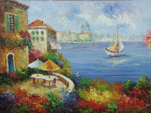 Beautiful medium sized painting, stretched but without frame, by Damini.  Pink, blue and yellow flowers surround a tan villa with a table set for two on a balcony facing a large sailboat in the light blue sea below.