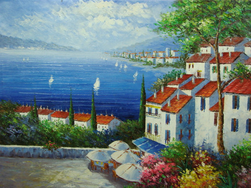 Beautiful painting, stretched but without frame, by Damini.  Tables sit at the edge of a large stone balcony near white villas that overlook sailboats floating in blue water.