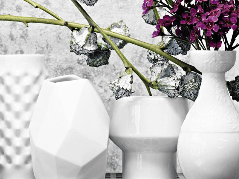 Four white Rosenthal Vases with purple flowers on gray background