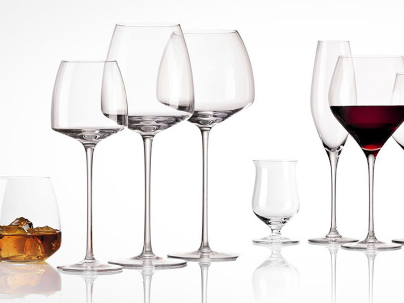 Various Rosenthal wine and whiskey glasses on mirrored surface.