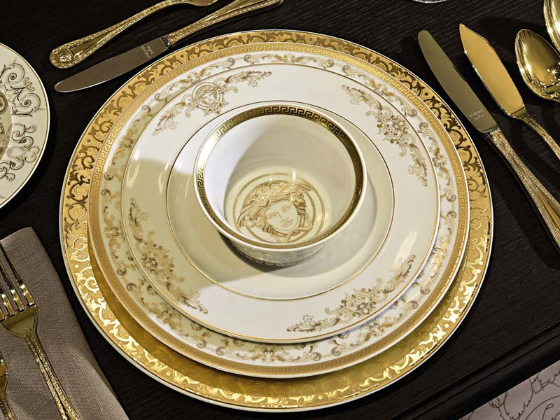 Versace Medusa Gala service plate, dinner plate, salad plate and cream soup cup, stacked on dark table linen.