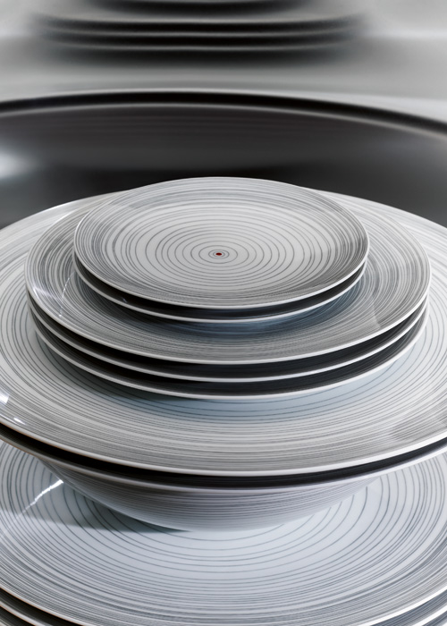Rosenthal TAC stripes table setting with stacked plates and a soup cup on top on a dark table surface.