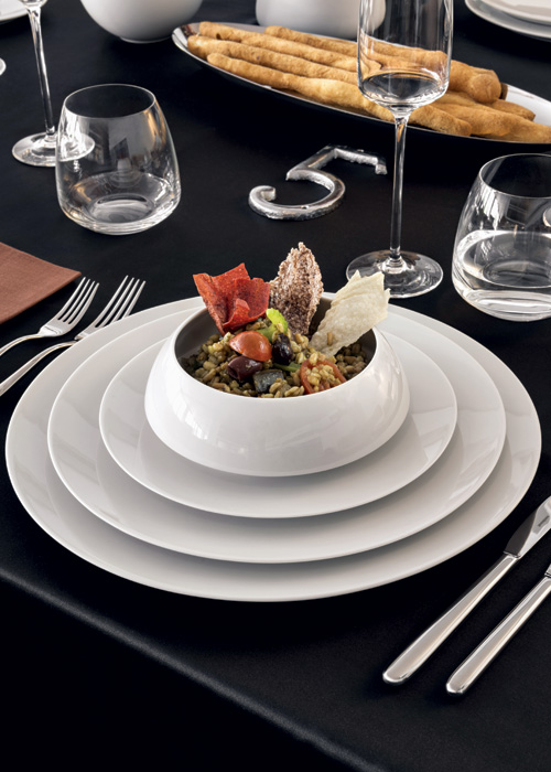 Rosenthal TAC 02 White table setting with stacked plates and a soup cup on top on a black table surface.
