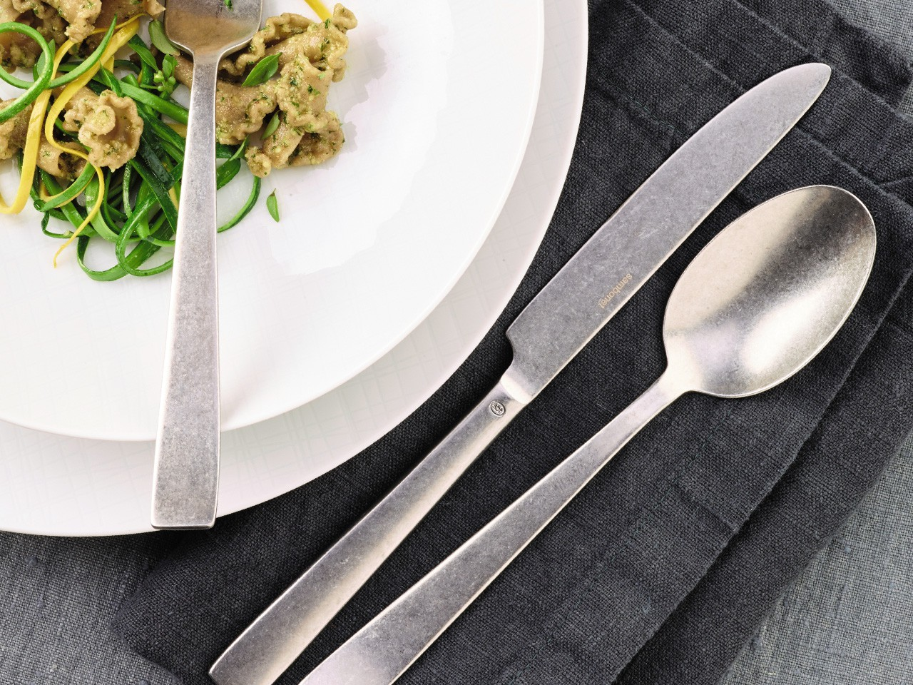 Sambonet Vintage Flat flatware next to Rosenthal Jade dinnerware on gray linen cloth.
