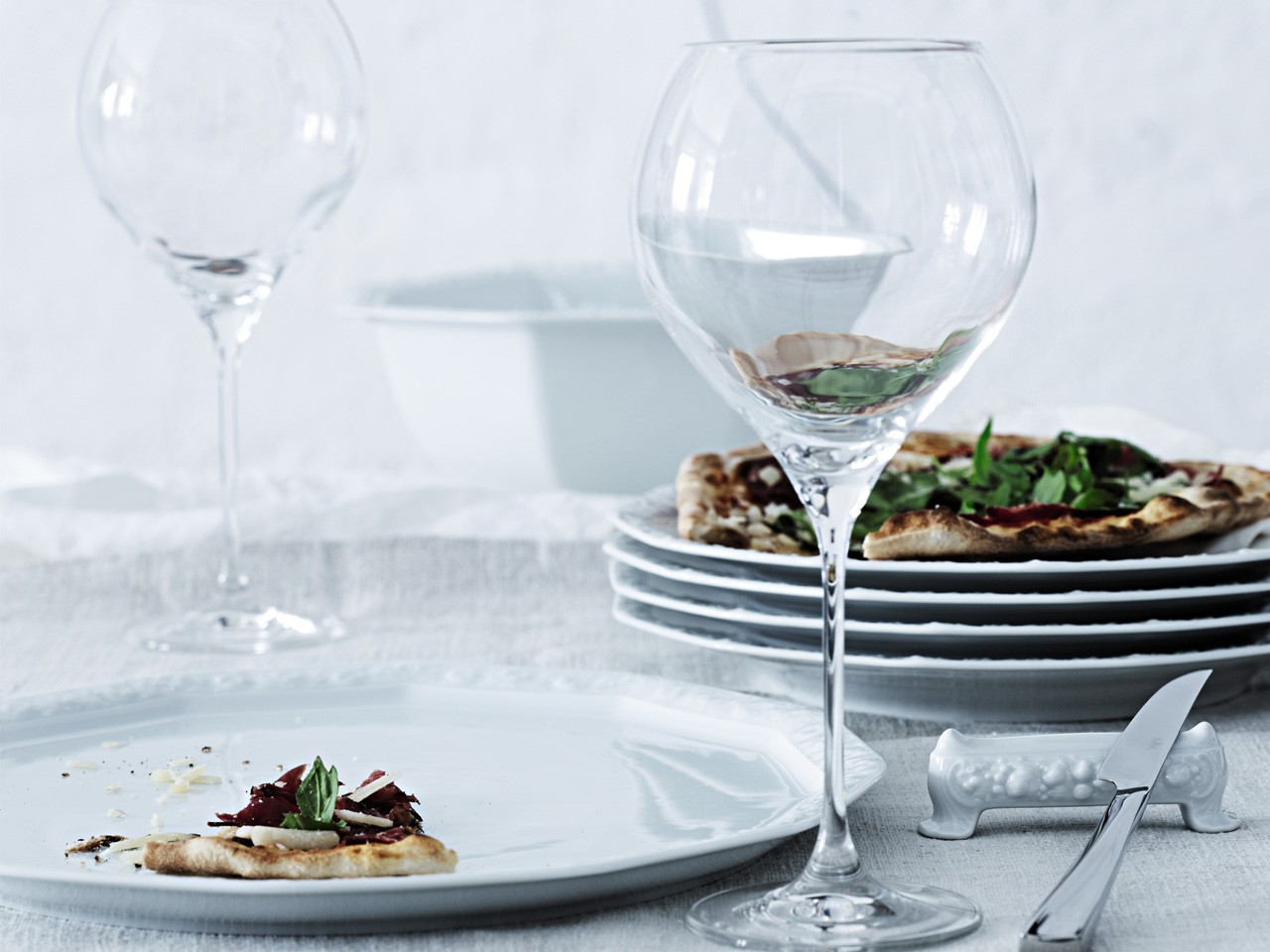 Rosenthal Maria White plates, stacked with pizza on top in the background. In the front white dinner plate with wine glass.