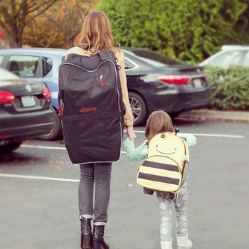 Woman carrying Diono Car Seat Travel Bag on her back alongside her child [Black]