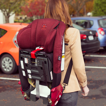 Woman carrying car seat on her back using the Diono Radian® and Rainier Car Seat Carrying Straps [Black]