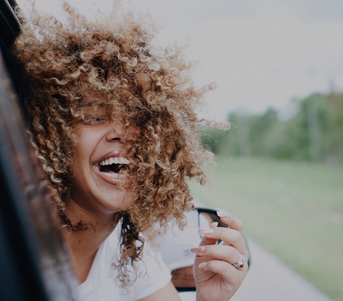 Laughing woman leans out car window, beautiful curls blowing in the wind.