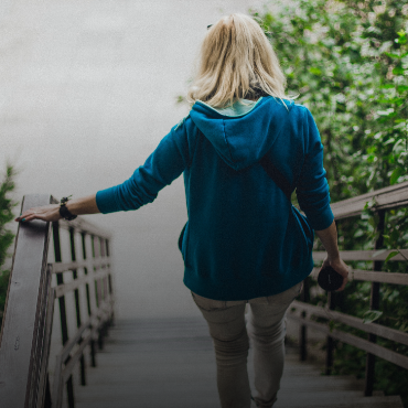 Mature woman walks down an outdoor staircase.