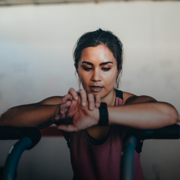 Young, healthy woman checks her fitness watch during a workout.