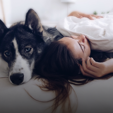 Sleeping woman snuggles with her dog in bed