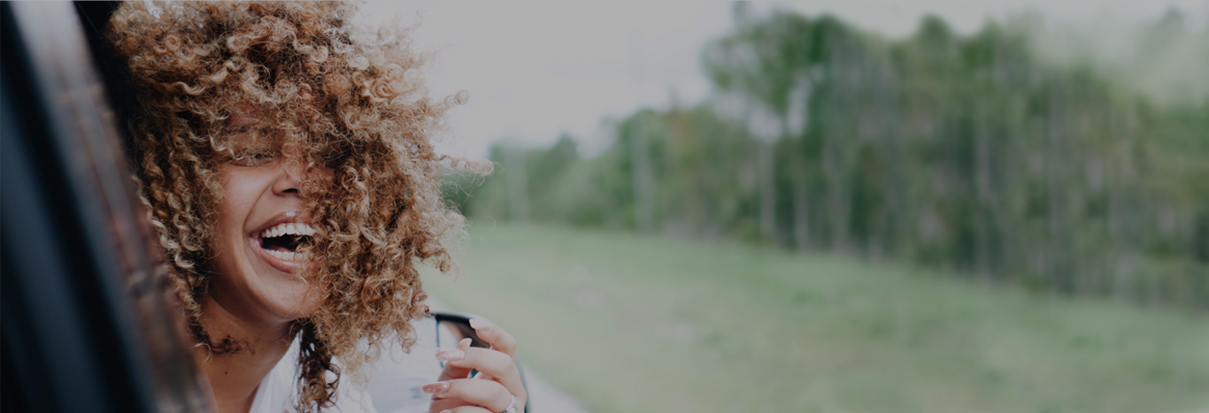 Laughing woman leans out car window, beautiful curls blowing in the wind