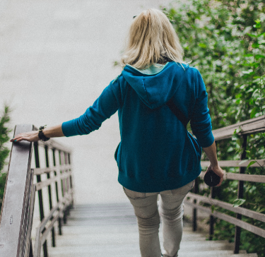Mature woman walks down an outdoor staircase