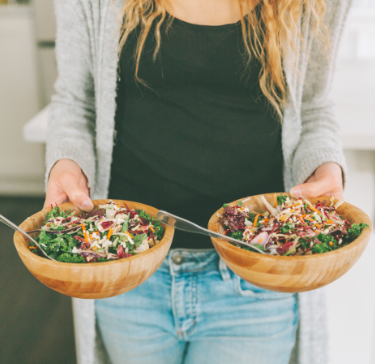 Woman holds two bowls full of healthy, whole-food meals