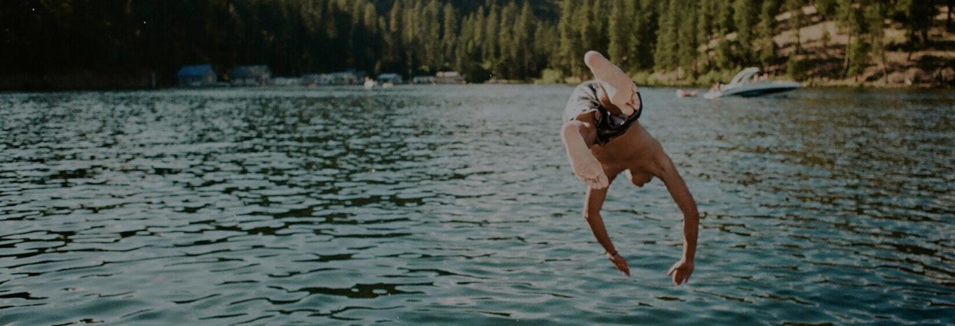Young man dives headfirst into beautiful, natural lake