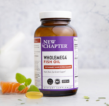 Fish oil supplement surrounded by herbal ingredients and extra-virgin oil from wild Alaskan salmon