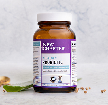 Probiotic supplement surrounded by herbal ingredients with a mortar and pestle