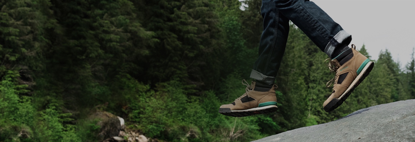 Person's legs and feet in mid-air, jumping above a rock on a hike