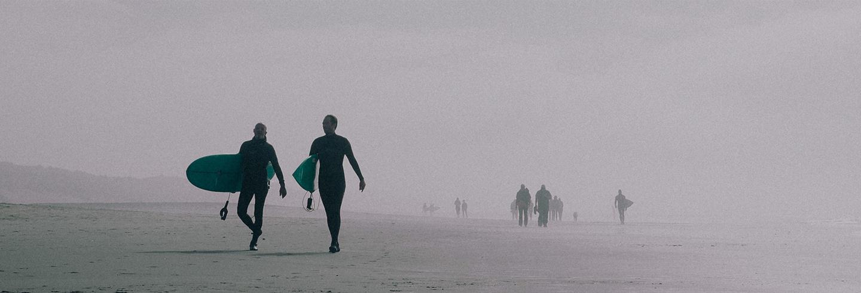 Mature man walks on beach, balancing surfboard on his head