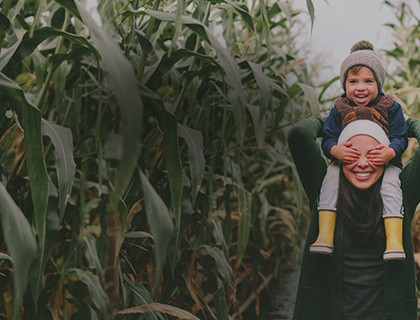 Young mom carries her playful child on her shoulders, walking through a corn field