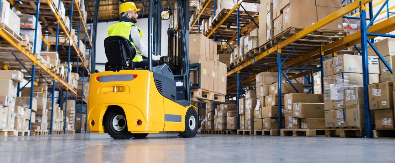 man with yellow vest and helmet operating forklift in warehouse