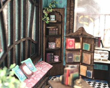 1:48 quarter scale corner shelf with the books and boxes, shown in the Joie de Vivre Bookshop.