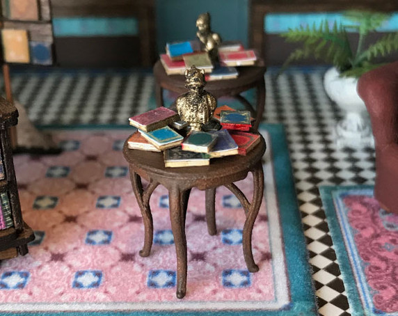 Two 1:48 quarter scale display tables with books and busts.