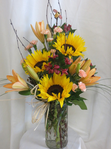 "Our Buzzing Beautiful Sunflower and Orange Lily Bouquet is buzzerific! A beautiful bouquet of flowers for the bumble bee to fly around. Includes the bumble bee, sunflowers, orange lilies, alstroemeria, pixie carnations, branches, and a raffia bow. Approximately 26""H x 16""W  For local delivery only. SKU RM121"