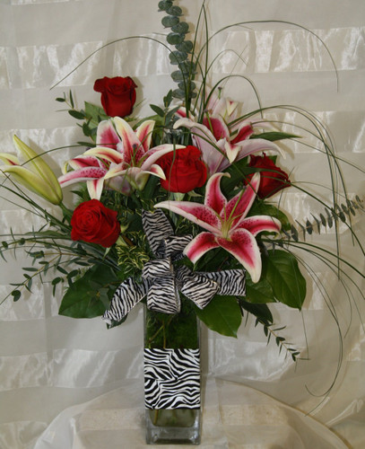 """The Wild Zebra Red Roses and Stargazer Lilies Bouquet. Send flowers that will stand out. Zebra print is all the rage and this bouquet includes fragrant stargazers lilies, classic red roses, and wild for you bear grass. Approximately 27""""H x 17""""W.  For local delivery only. SKU RM127"""